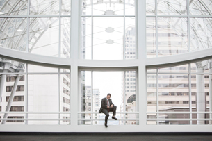 A Caucasian businessman using his phone while sitting on a railing by a windowの写真素材 [FYI02263915]