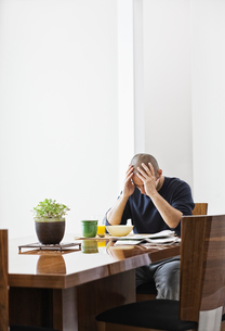 Hispanic man under stress while sitting at the dining room table in a new home.の写真素材 [FYI02263920]