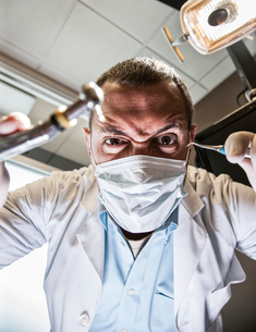 A dramatic view looking up from a patient's perspective of a scary looking dentist holding tools.の写真素材 [FYI02263921]