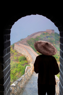 Rear view of man wearing traditional straw hat standing in arched doorway overlooking Great Wall ofの写真素材 [FYI02263934]