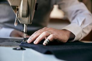 Man using an industrial sewing machine, stitching a garment.の写真素材 [FYI02263939]