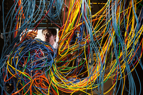 Asian male technician working on a tangled mess of CAT 5 cables in a server room.の写真素材 [FYI02263951]