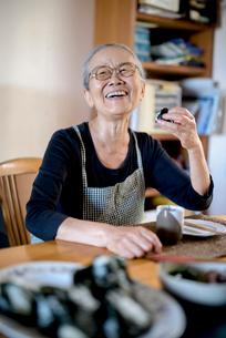 Elderly woman sitting at kitchen table, eating sushi, smiling at camera.の写真素材 [FYI02263965]