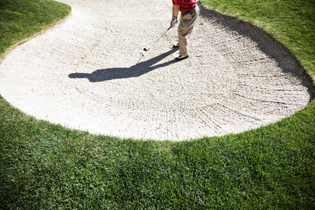Senior golfer playing out of a bunker on the golf course.の写真素材 [FYI02263969]