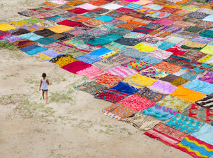 High angle view of boy standing on a field with a large number of colourful cotton fabrics spread ouの写真素材 [FYI02263978]