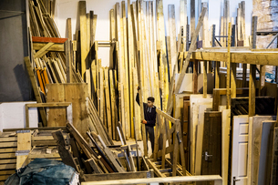Interior view of warehouse with stacks of wooden planks, young man working.の写真素材 [FYI02263983]