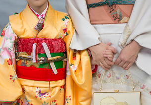 Close up of woman and child holding hands, wearing traditional Japanese kimonos standing side by sidの写真素材 [FYI02263986]