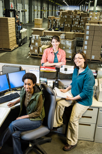 A team of three female warehouse workers at the front desk of a distribution warehouse.の写真素材 [FYI02264000]