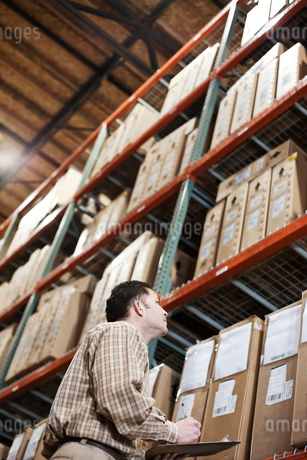 A storeroom manager looking at stock stacked high on shelves making notes with a clipboard and pen.の写真素材 [FYI02264004]