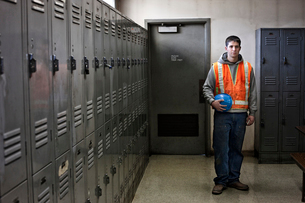 View of a young Caucasian factory worker wearing a safety vest and standing next to lockers in a facの写真素材 [FYI02264008]