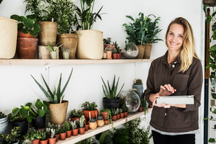 Female owner of plant shop standing next to a selection of plants on wooden shelves, holding digitalの写真素材 [FYI02264019]