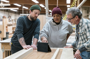 A group of mixed race carpenters discussing a project at a work station in a large woodworking shop.の写真素材 [FYI02264022]