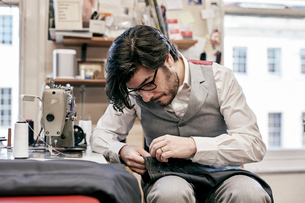 Man sewing suit by hand in family tailor businessの写真素材 [FYI02264027]