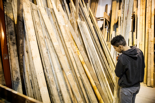 Young man standing next to a stack of wooden planks in a warehouse.の写真素材 [FYI02264028]