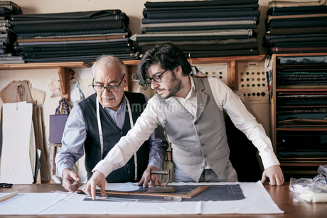 A tailor and a younger man, an assistant or apprentice working together, measuring cloth and cuttingの写真素材 [FYI02264040]