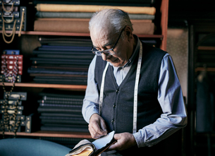 Tailor with measuring tape around his neck inspecting fabric samples.の写真素材 [FYI02264055]