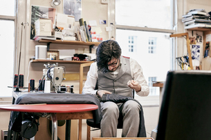 Man sewing suit by hand in family tailor businessの写真素材 [FYI02264056]