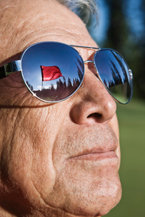 A golf flag on a green reflected in the sunglasses of a senior golfer.の写真素材 [FYI02264060]