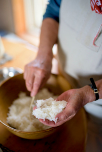 Close up of woman standing at a table in a kitchen, making sushi.の写真素材 [FYI02264061]