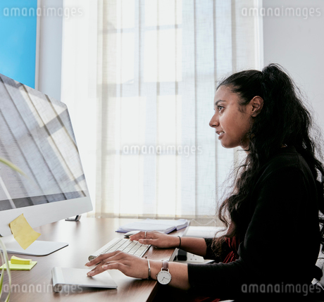 Woman sitting at a desk in an office using a computer keyboard and looking at a screen.の写真素材 [FYI02264068]