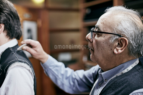 Tailor fitting a jacket on a customer using tailor's chalk to mark the fabric.の写真素材 [FYI02264077]