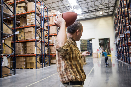 Warehouse employees playing catch with an American football during a work break in a distribution waの写真素材 [FYI02264095]