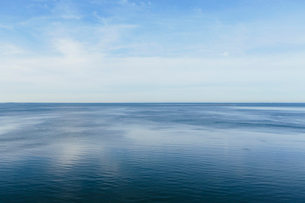 View out to the open sea from the coast. Flat calm water surface.の写真素材 [FYI02264100]