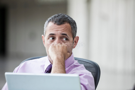 A Caucasian businessman pondering a problem while working on a laptop computer.の写真素材 [FYI02264102]