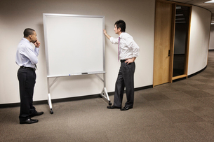 A black businessman and an Asian businessman ponder the issue of an empty white board.の写真素材 [FYI02264105]