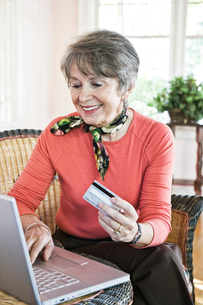 Senior woman buying a product online with a credit card.の写真素材 [FYI02264113]