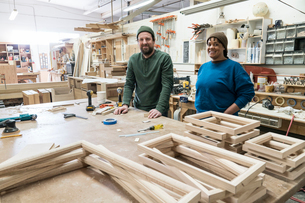Portrait of a team of two mixed race male and female carpenters in a large woodworking factory.の写真素材 [FYI02264114]