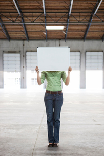 Woman holding up a blank slate in an empty warehouse space.の写真素材 [FYI02264117]