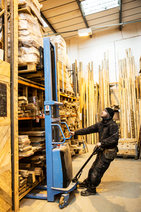 Man standing in warehouse using forklift to move pallet of wood off a shelf.の写真素材 [FYI02264120]