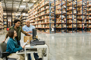 A group of three mixed race warehouse workers checking inventory on a computer in a large distributiの写真素材 [FYI02264123]