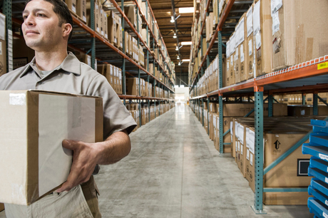 A view of a uniformed male Hispanic warehouse worker carrying a box down an aisle full of boxed prodの写真素材 [FYI02264135]