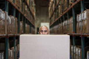A black warehouse worker hidden behind a cardboard box in a distribution warehouse.の写真素材 [FYI02264139]