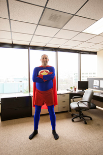 A self satisfied Caucasian office super hero in his cubicle office.の写真素材 [FYI02264140]
