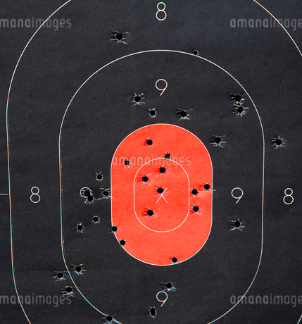 Close up of red and black shooting target with bullet holes.の写真素材 [FYI02264144]