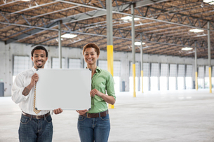 Black man and black woman holding up a blank slate in the interior of a brand new empty warehouse spの写真素材 [FYI02264150]