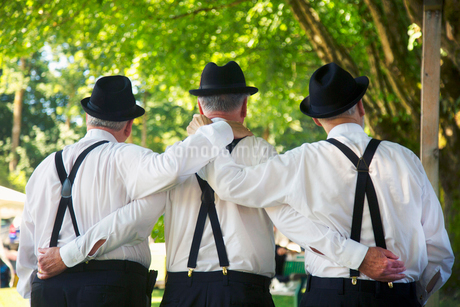 Rear view of three men wearing white shirts, black trousers with suspenders and hat standing side byの写真素材 [FYI02264155]