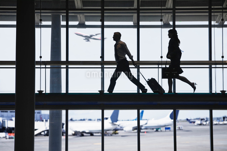 Businessman and business woman running to catch an airplane on an airport walkway.の写真素材 [FYI02264156]
