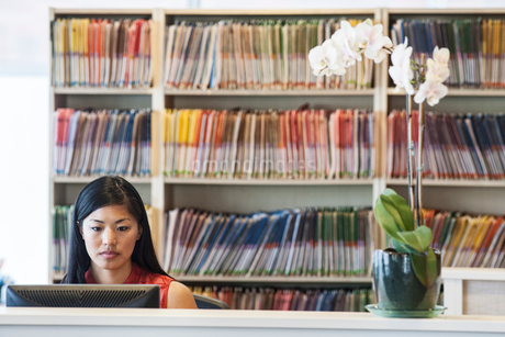 Asian female working in a medical office with file folders in the backgroundの写真素材 [FYI02264159]