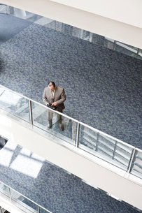View looking down on an Hispanic businessman checking his notebook computer on a walkway balcony ofの写真素材 [FYI02264161]