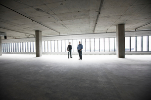 An architect and a business owner planning a new office space in an empty raw business space.の写真素材 [FYI02264162]