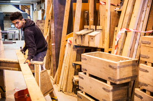 Young man wearing work gloves standing in warehouse, balancing plank of wooden on trestle, stack ofの写真素材 [FYI02264163]