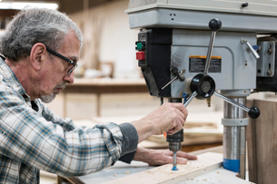 A senior man with glasses and beard in a woodworkers shop, using a machine.の写真素材 [FYI02264169]