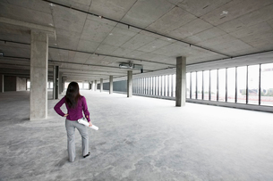 A woman architect holding architectural drawings looking out over a new raw business space.の写真素材 [FYI02264171]