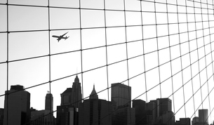 Skyline of Manhattan seen from Brooklyn Bridge, skyscraper, passenger plane in the sky, New York, USの写真素材 [FYI02264178]