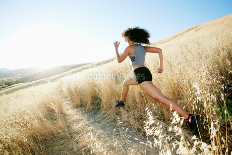 Young woman with curly brown hair running in urban park.の写真素材 [FYI02264180]