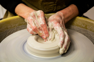 Close up of potter wearing apron working on pottery wheel, shaping clay vase.の写真素材 [FYI02264186]